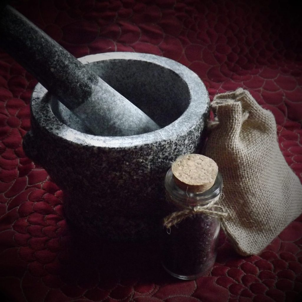 Gray granite mortar and pestle, small burlap bag, and glass bottle of black salt with a twine bow and cork..
