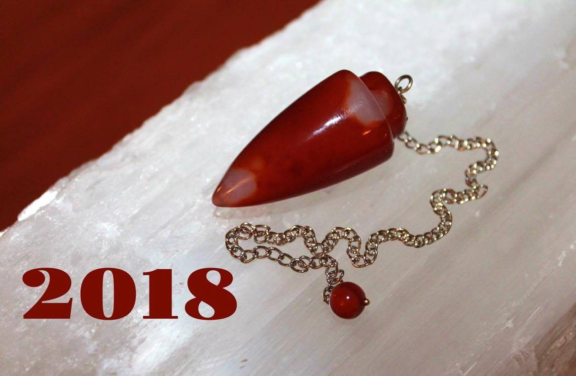 Red pendulum on selenite with new year 2018 in left lower corner